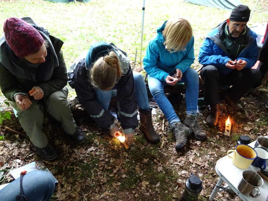 Cursisten zitten op houten boomstammen in een Twents bos en maken een vuurtje met een firestriker.