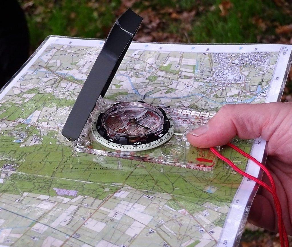 Cursist heeft een landkaart vast met daarop een kompas om te kijken waar zij naartoe moet.