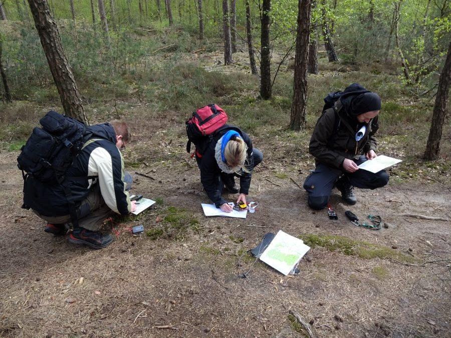 Drie cursisten met outdoorkleding en rugzak op, zitten op hun hurken een route uit te stippelen op een landkaart met kompas en gps in de bossen van de Sallandse Heuvelrug.