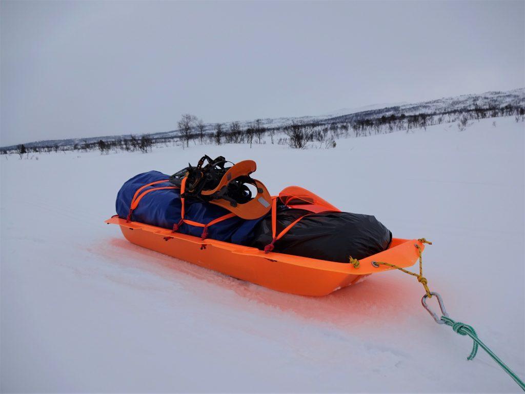 Oranje expeditieslede beladen met outdoorspullen en sneeuwschoenen wordt getrokken door een wit sneeuwlandschap in Noorwegen.