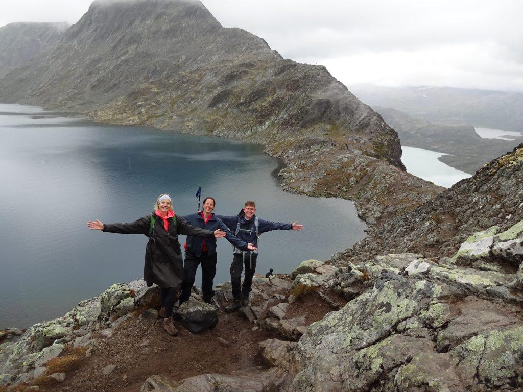 Groepsfoto cursisten Northern Pioneers staande hoog op rotsen met achter hen laag een meer en ruige bergen
