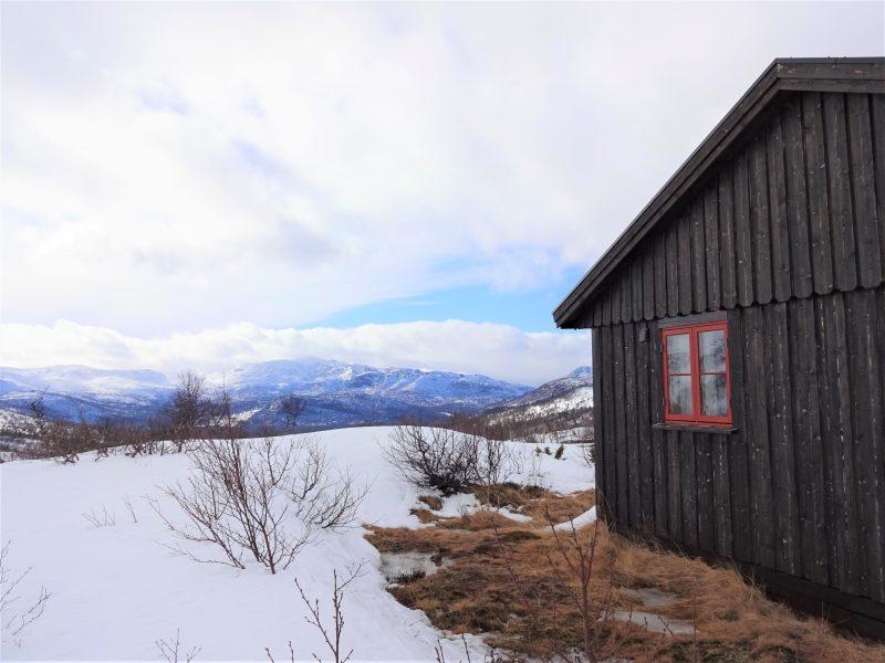 Links zie je een besneeuwd berglandschap met een wolkenlucht en rechts staat een donkerbruin hutje met een rood beschilderd raam met 4 vakken.