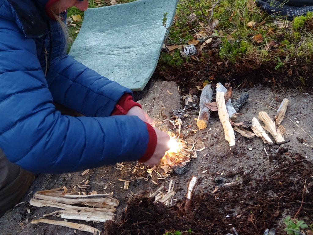 Cursist maak een kampvuur met een firestriker en rondom liggen klein gesneden stukken hout tijdens een rugzaktrektocht in Noorwegen.