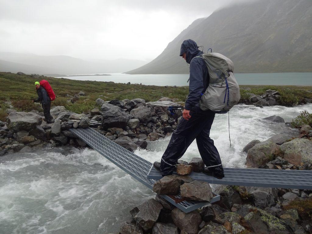 Hiking cursisten met rugzak die een klein wild riviertje oversteken over een smal metalen platen die fungeren als bruggetje met uitzicht op bergen in de mist in Noorwegen
