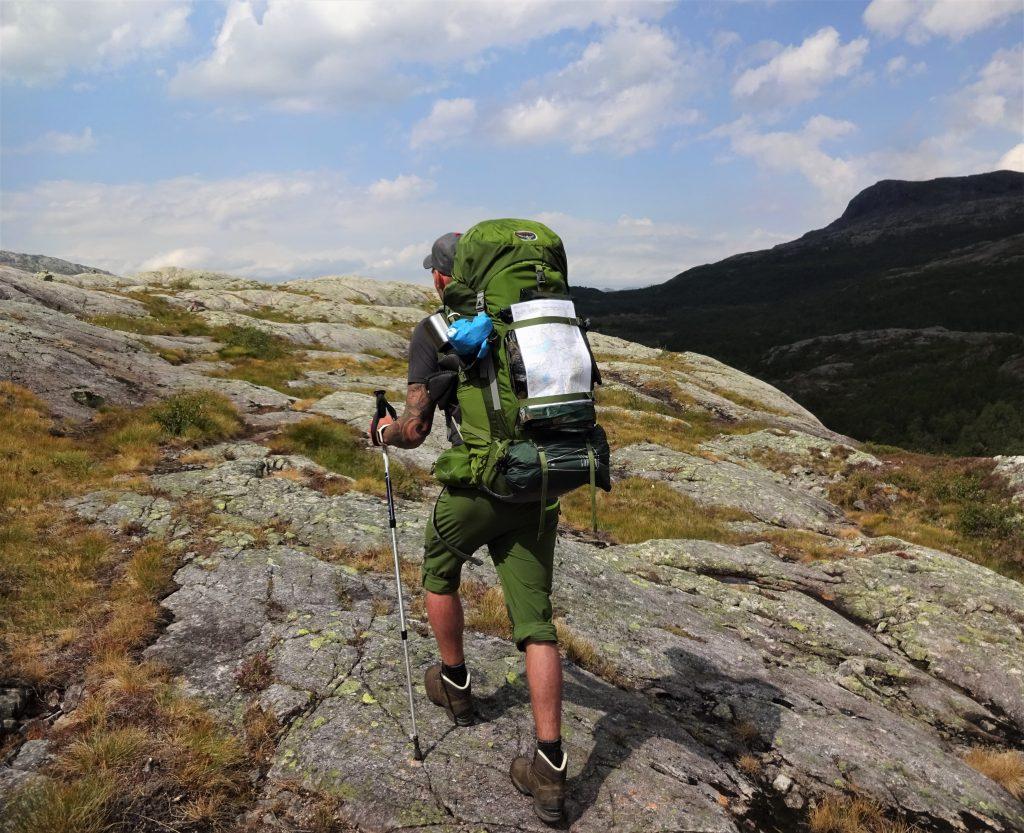 Cursist rugzaktrektocht hiked met rugzak en wandelstok over rotsachtig heuvels in het ruige berggebied in Noorwegen Setesdal.