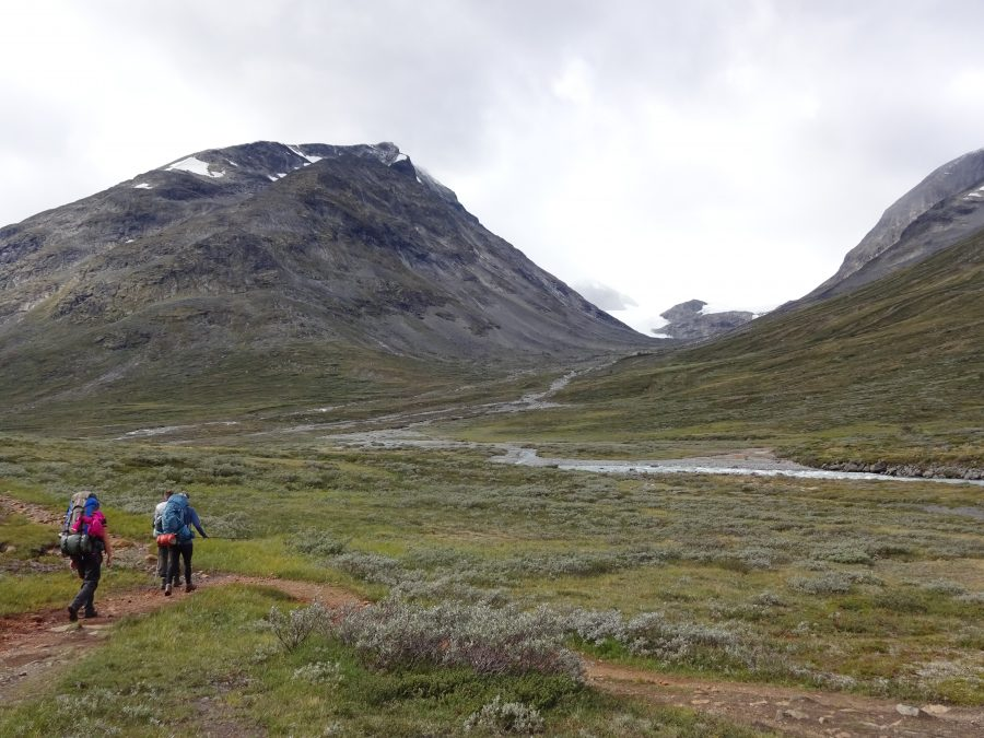 Cursisten hiken door dal met uitzicht op bergen in Noorwegen