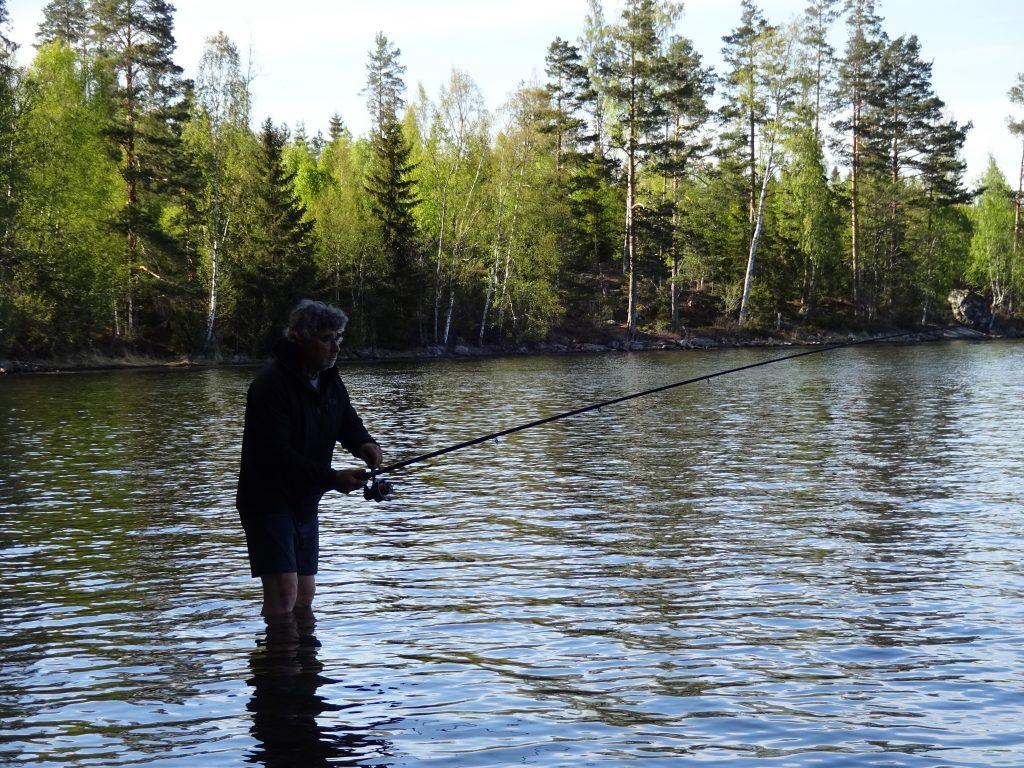 Cursist staat met blote onderbenen in het water te vissen in een meer met uitzicht op bos in Zweden.