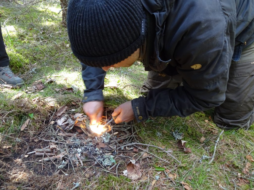 Mannelijke cursist in outdoorkleding maakt vuur aan met een firestriker in een natuurgebied in Zweden.