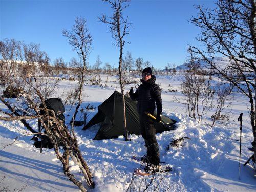 Stagiair van Northern Pioneers staat tijdens zijn stage bij een erkend leerbedrijf van SBB voor zijn tarp in de sneeuw in Noorwegen.
