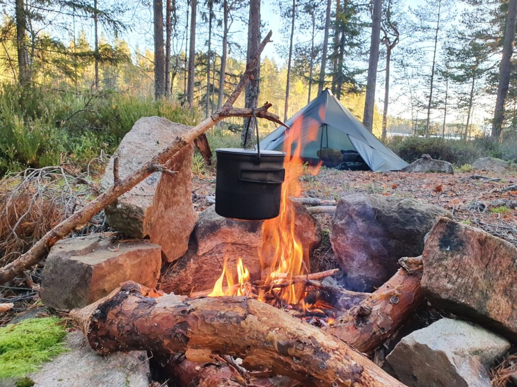 Kampvuur en tarp tijdens solotrekking in Zweden